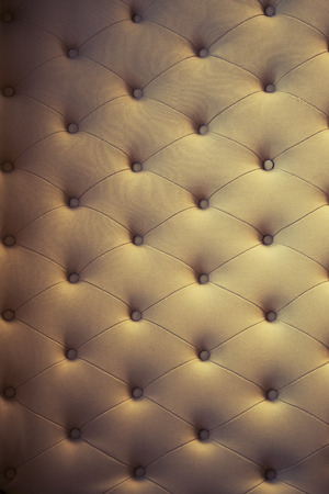 extravagance: brown couch background texture with sunken buttons.