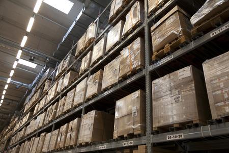 Rijen van rekken met dozen in fabriekspakhuis