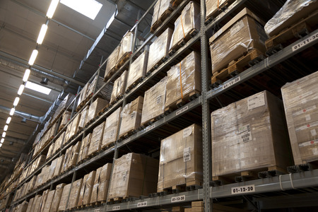 Rows of shelves with boxes in factory warehouse Stock Photo