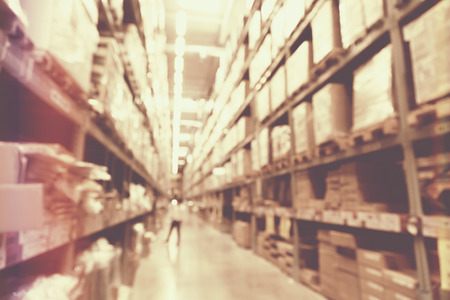 empty warehouse: blurred image of boxes in factory warehouse with light leak filter. Stock Photo