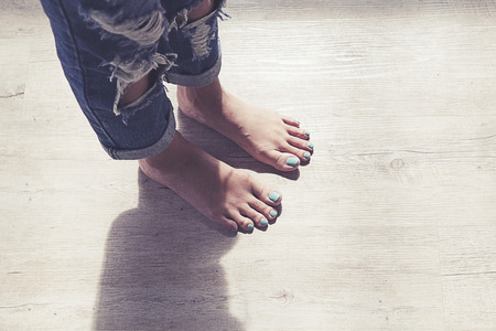 wooden floors: Feet of girl on wooden floor.