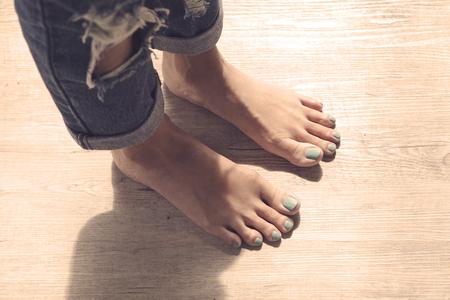 Feet of girl on wooden floor.
