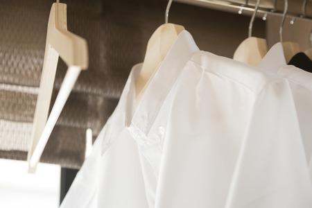 book racks: white shirts hanging on white built-in cloths racks