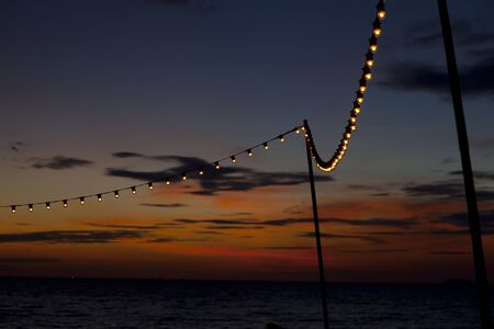 subset: Lamp string hanging against subset sky by the sea