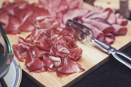 hams: La selecci�n de jamones y salami sobre tabla de cortar de madera de �poca
