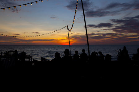 Lamp string hanging against subset sky by the sea