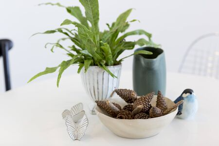 white table with tree pot,vase,bird sculpture and dried pine cones Stock Photo