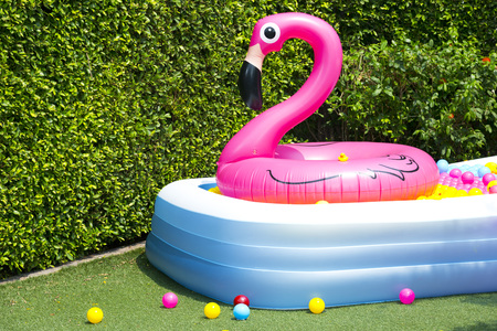 inflatable pool with flamingo balloon in garden