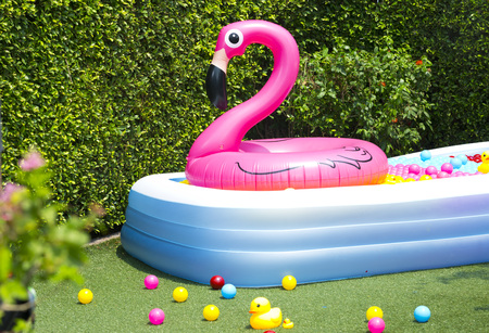 opblaasbaar zwembad met flamingo ballon in de tuin Stockfoto