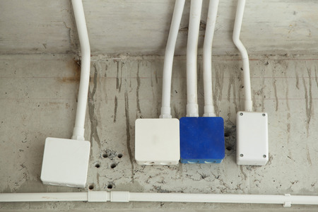 plastic conduit: four electrical junction boxes with plastic conduit pipe connection Stock Photo