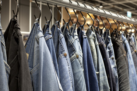 mass storage: A row of jeans hanging on the rack Stock Photo