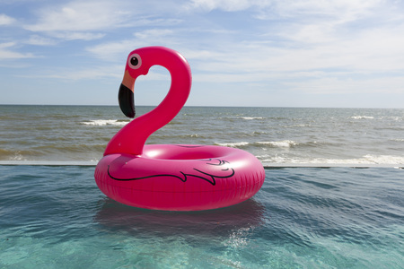 Air flamingos balloon float in the swimming pool by the sea Foto de archivo