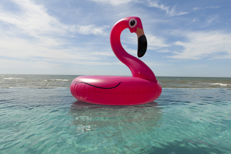 air: Air flamingos balloon float in the swimming pool by the sea Stock Photo