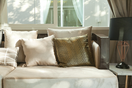 beige cushion on grey sofa 免版税图像 - 84391660