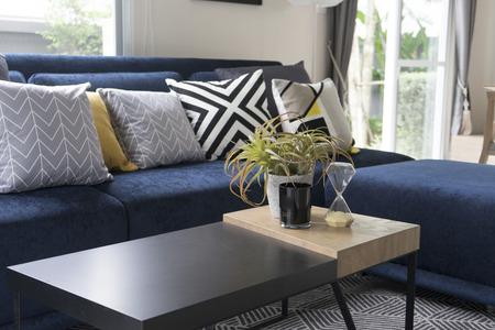 grafisch patroon kussen op blauwe bank met plant pot op tafel Stockfoto