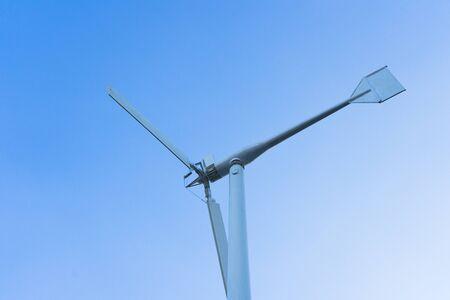 Wind turbines over blue sky with sun