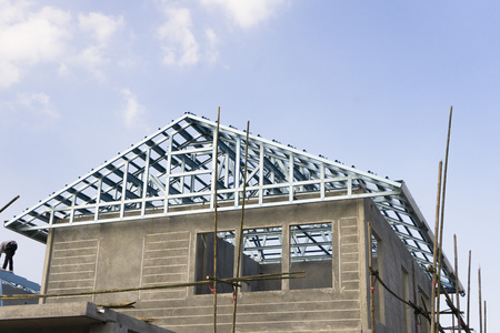 Construction site of new home with roof frame and blue sky