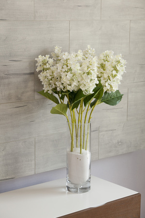 Bouquet Of White Flower In A Vase On A Table In Room Corner Stock