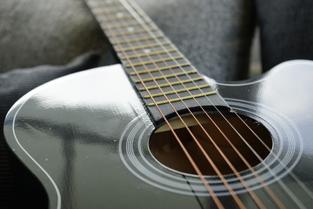 six stringed acoustic guitar on grey sofa