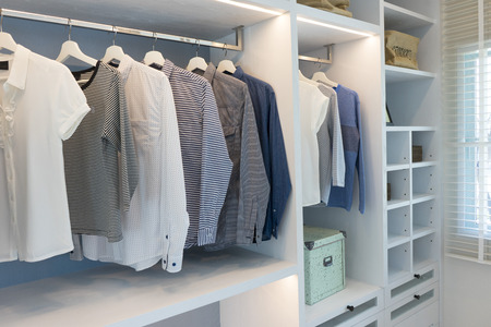 Black and white cloths hanging in wooden wardrobe at home