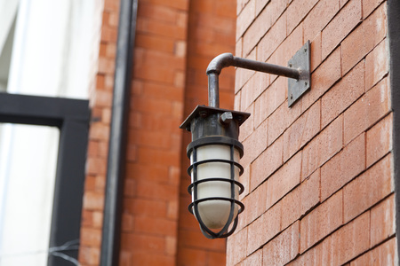 Black wall lamp on brick wall at outdoor