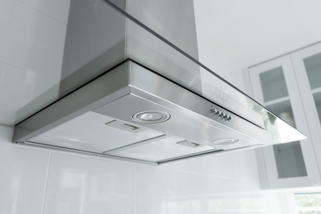Metal cooker hood extractor fan with spotlight in luxury kitchen.