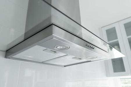 Metalowy wentylator okapu z oświetleniem punktowym w luksusowej kuchni.