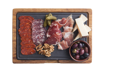 Platter with olive, parma ham, salaminho,cheeses and salami with glasses of red wine on old wooden board Foto de archivo