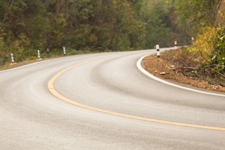 sharp curve road in forest hill Stock Photo