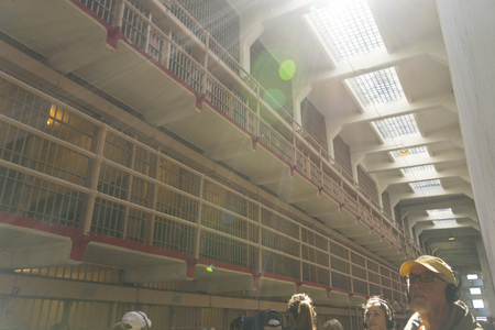 Tourists visiting Alcatraz prison and the main corridor with ordinary single cells on ground level. San Francisco historical landmark