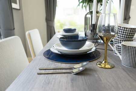 Modern dinning interior with clean white plates, glasses and cutlery on wooden table