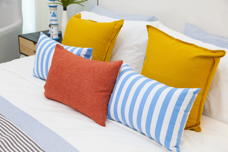 orange, yellow and blue pillows on white bed at home Stockfoto