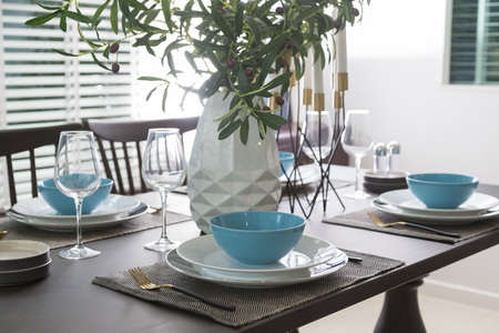Modern dinning room interior with blue plate on wood table at home. Stock Photo