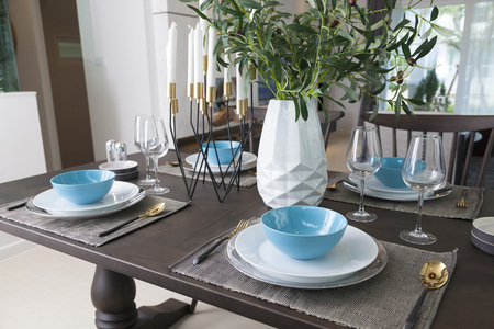 Modern dinning room interior with blue plate on wood table at home. Stock Photo - 117521230