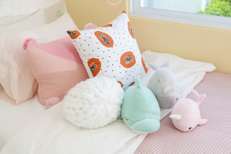 Cute teddy bears and dolls on bed for little girl