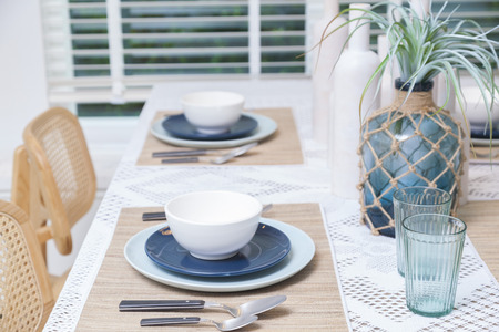 Rustic table setting with blue plate, cutlery and glass vase in home dinning room