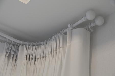 Las cortinas blancas con la decoración interior de la cortina del riel superior del anillo en la sala de estar