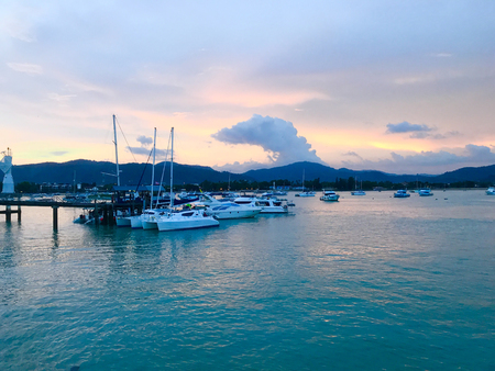 Sunset view of Chalong Bay Pier, luxury yachts and sailboats port in Phuket Thailand