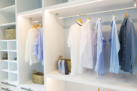 white modern wardrobe with black and blue cloth hanging.