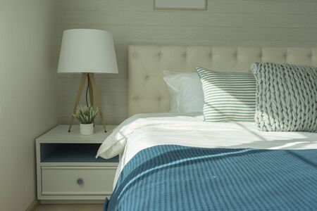 Close up side view of the pillows and headboard with white linen  bed.