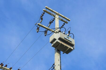 Electric distribution transformer pole and blue sky. Archivio Fotografico