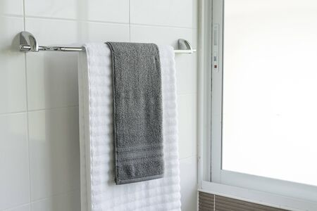 white towels Hanging on a hanger in the bathroom
