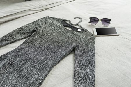 Luxury black woman dress with sunglasses and smartphone on bed, woman prepare to dress up.