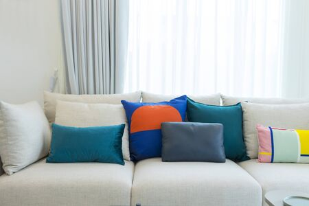 Large white sofa with colorful cushions in a spacious living room interior with green plants and white walls.