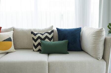 Gran sofá blanco con cojines de colores en el interior de una amplia sala de estar con plantas verdes y paredes blancas. Foto de archivo