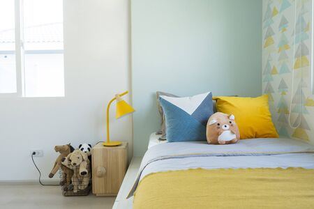 Kid bedroom in blue and yellow tone pillow with many doll on bed. Stock Photo