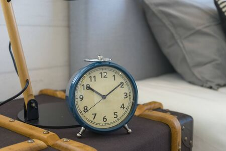 Blue alarm clock standing on nightstand beside bed in interior of room. Banque d'images