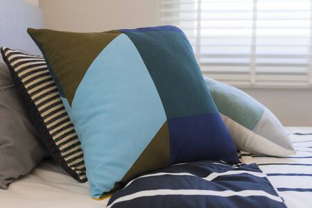 Graphic blue pattern pillow on bed in boy bedroom.