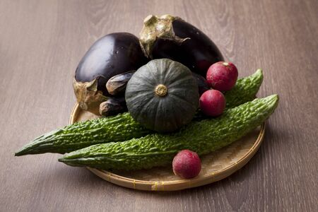 Fresh Angled loofah,Angled Gourd,eggplant and pumpkin on wood table 写真素材
