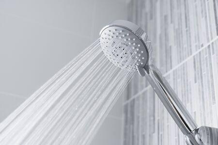Bathroom shower head spraying water on blue background